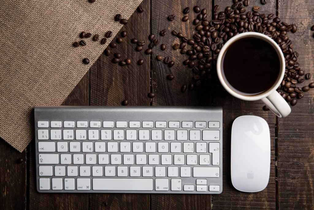A keyboard, mouse and coffe mug on a table.